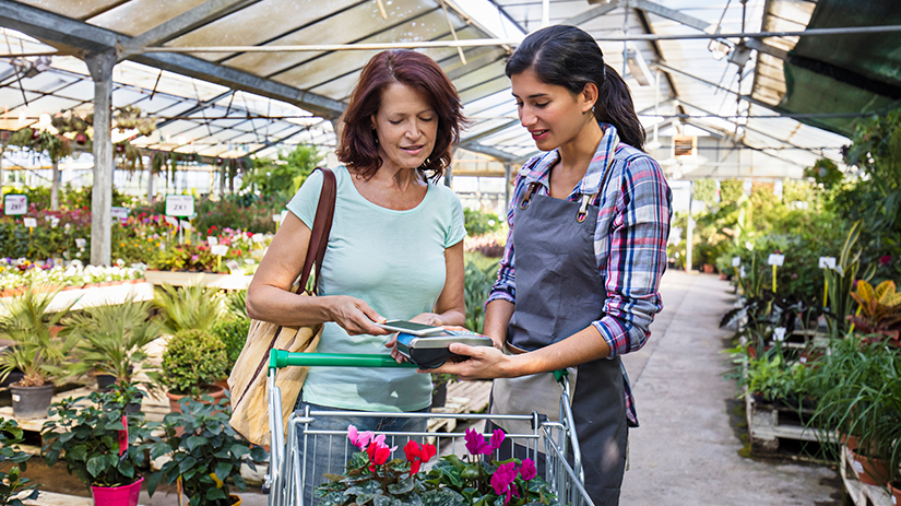 woman paying with smartphone at plant nursery