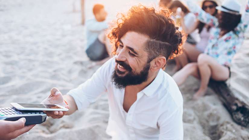 man paying with a smartphone on the beach