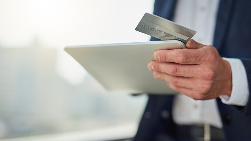 man using tablet and credit card