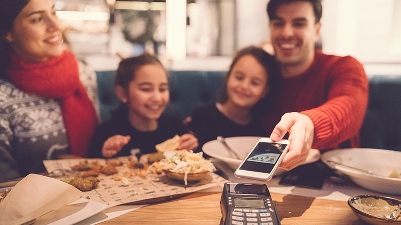 family in restaurant paying contactless