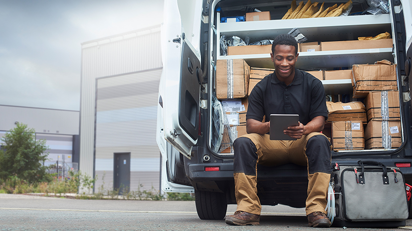 service engineer sitting at the back of his van